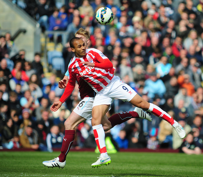 Stoke City's Peter Odemwingie gets to a header under pressure from Burnley's Ben Mee<br /> <br /> Photographer Andrew Vaughan/CameraSport<br /> <br /> Football - Barclays Premiership - Burnley v Stoke City - Saturday 16th May 2015 - Turf Moor - Burnley<br /> <br /> &copy; CameraSport - 43 Linden Ave. Countesthorpe. Leicester. England. LE8 5PG - Tel: +44 (0) 116 277 4147 - admin@camerasport.com - www.camerasport.com