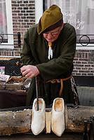 Man maakt klompen in middeleeuwse klederdracht