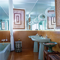 The 1970's bathroom has a pair of matching free-standing basins, a floor and wall tiles of cork and windows with Moroccan screenwork