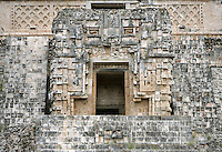 Entrance to The Temple of the Magician or House of the Dwarf, c. 900 AD, Puuc architecture, Uxmal late classical Mayan site, flourished between 600-900 AD, Yucatan, Mexico. On both sides of the entrance, panels with calendric or astronomic hieroglyphs. Above the nose of the huge mask, an empty niche which may contain the statue of an importanty personnage on a pedestal held up by two kneeling slaves. On each corner, masks of Chaac, as well as on the middle of the staircase. Picture by Manuel Cohen