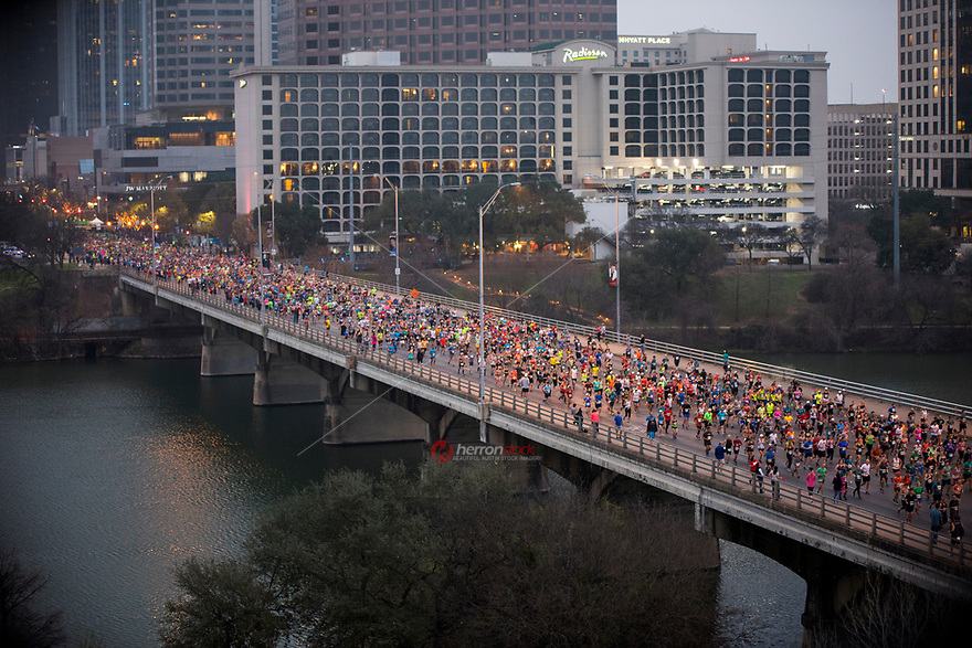Thousands of Austin Marathon runners fill overtake the Congress Avenue Bridge after the starting pistol sounds during the annual Austin Marathon in downtown Austin, Texas.<br />