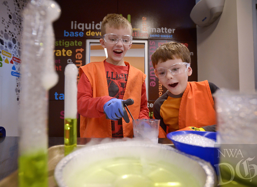 NWA Democrat-Gazette/BEN GOFF @NWABENGOFF<br /> Dominic Furlano (left), 9, and Jerry Davis, 6, both of Bentonville, observe how bubbles form in various containers after adding a piece of dry ice to soapy water on Monday Jan. 16, 2017 during the I.C.E.: Investigate, Create and Explore All Things Frozen day camp at the Scott Family Amazeum in Bentonville. The camp engaged children age 6-11 with the science of cold, with activities that included making ice sculptures, observing how liquids freeze and experiments with dry ice.