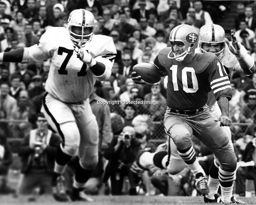 San Francisco 49ers QB George Mira scrambles away from Oakland Raiders Issac Lassiter and Dan Birdwell..(photo by Ron Riesterer)