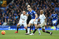 Tom Cleverley competes with Andre Ayew during the Barclays Premier League match between Everton and Swansea City played at Goodison Park, Liverpool