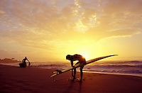 A surfer and body boarder on a North Shore beach during sunset with boards in hand