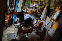 A Colombian hairdresser sits in a wooden armchair while waiting for the customers in his barber shop in the market of Bazurto in Cartagena, Colombia, 14 April 2018.