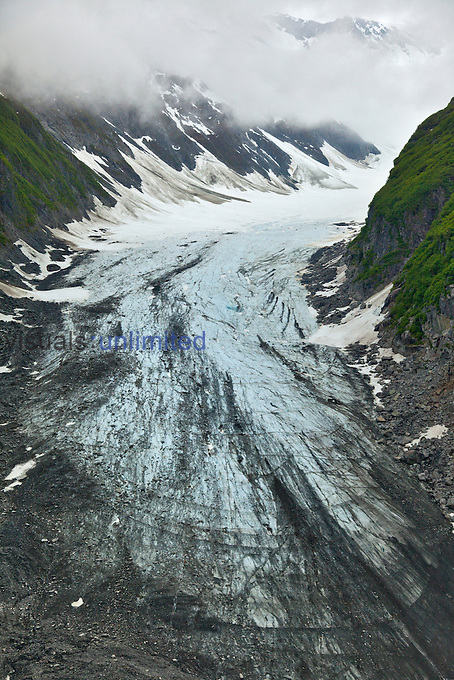 Aerial view of a valley glacier flowing from the mountains to its terminus, Alaska, USA