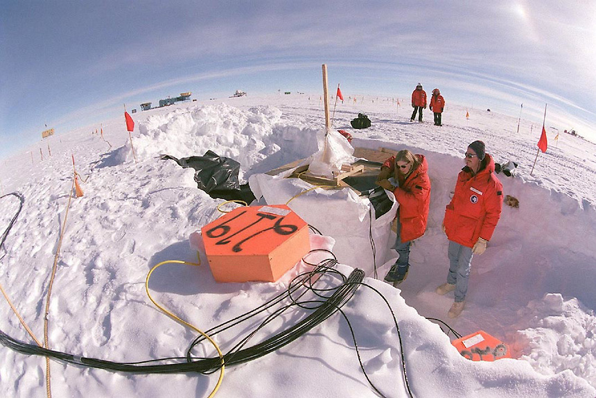 Univeristy of Wisconsin physics graduate student Katherine Rawlins (foreground, left) and UW-River Falls physicist James Madsen examine an experiment related to the proposed Ice Cube neutrino detector at the Amundsen-Scott South Pole station on Jan. 5, 2001. Rawlins and Madsen were at the South Pole to work on  AMANDA, a functioning neutrino detector that is a smaller version of the proposed Ice Cube, which recently received $15 million from Congress.  Both experiments make use of highly sensitive instruments buried up to two and a half kilometers deep under the South Pole ice.