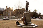February 23, 2015. Durham, North Carolina.<br />  Robbie Florian, a senior in Visual and Media Studies, reads a Harry Potter book aloud, asJessica Van Meir listens, at the foot of a statue of James Buchanan Duke. Duke  was the son of Washington Duke, who founded Trinity College, which became Duke University.