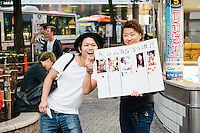 "Two young men in Shibuya. The poster reads ""If you were to become friends, who would you choose?"""