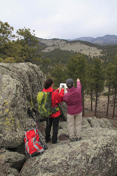 Two women navigating with map and compass. Front Range Mountains, Colorado.