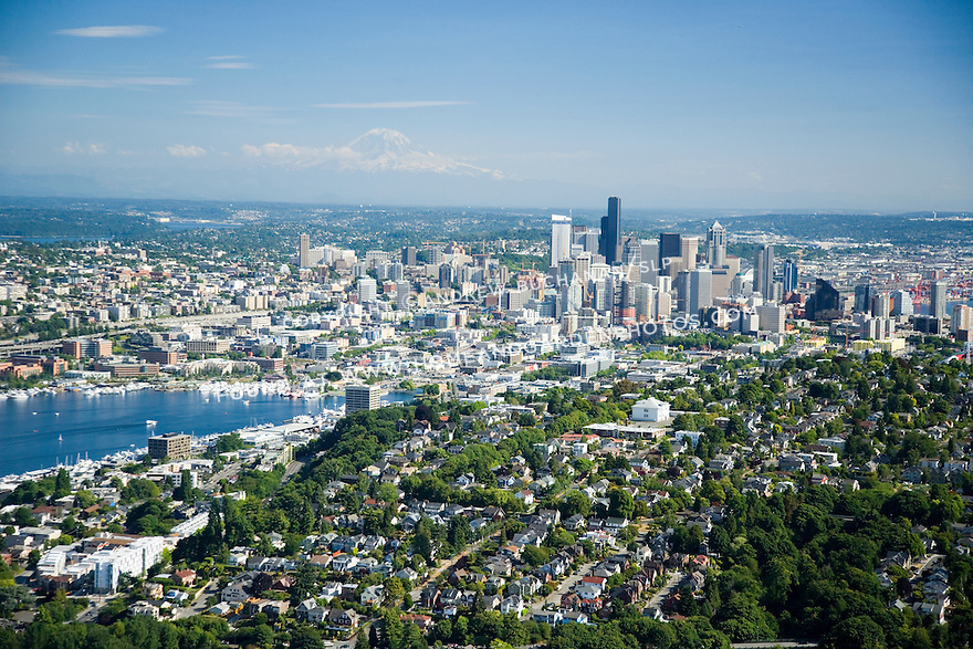 A sunny, summer afternoon aerial photo of Seattle, Washington showing green and leafy Queen Anne Hill in the foreground, Lake Union, the skyscrapers of the downtown skyline, and snow-capped Mount Rainier in the distance in this classic image of a modern Northwest city.