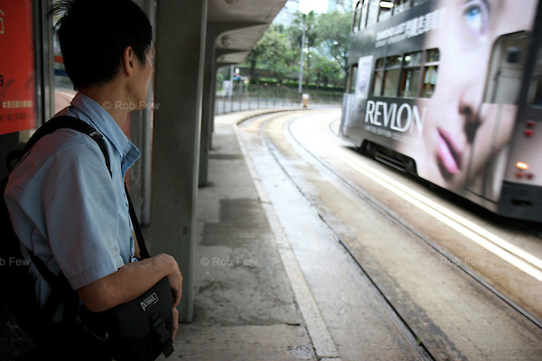 After a night's fitful sleep on the pier to show his support, this teacher waits for a tram to take him to his job for a full day's work.<br /> <br /> In late May 2007, academics, students and members of the general public occupied Queen's Pier in central Hong Kong. They were protesting against the government's decision to demolish the pier to make way for a new development. The protesters were determined, but the odds were stacked firmly against them.