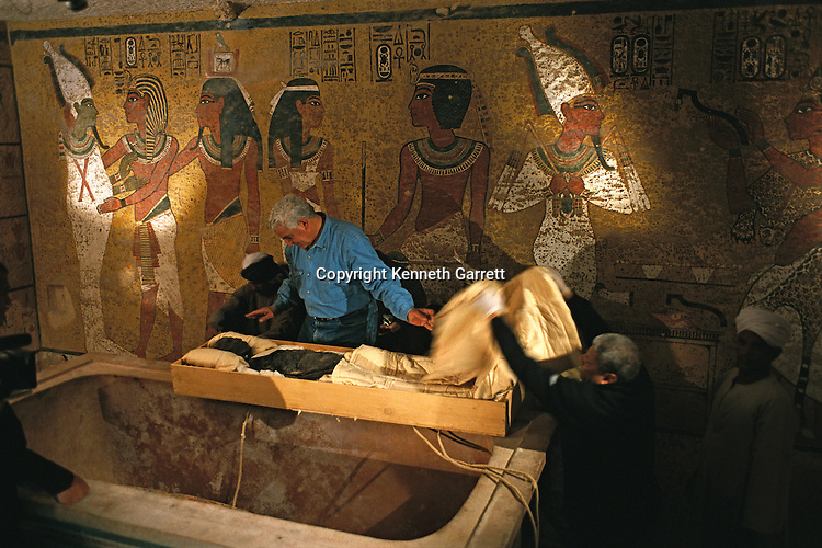 Archaeologist Dr. Zahi Hawass examines the mummy of Tutankhamun in his tomb, the mummy readied for transport for CT scanning, Tutankhamun and the Golden Age of the Pharaohs; page 264;Egyptian Mummy Project,18th dynasty; New Kingdom; Tutankhamun; Thebes; Valley of the Kings; KV62