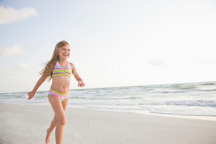 USA, Florida, St. Pete Beach, Smiling girl (8-9) in bikini walking on beach
