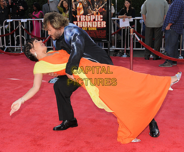 "TANYA HADEN & JACK BLACK.The Dreamwork's L.A. Premiere of ""Tropic Thunder"" held at The Mann's Village Theatre in Westwood, California, USA..August 11th, 2008.full length black suit orange dress yellow scarf married husband wife blue print lightning holding funny gesture dancing bending leaning dip .CAP/DVS.©Debbie VanStory/Capital Pictures."