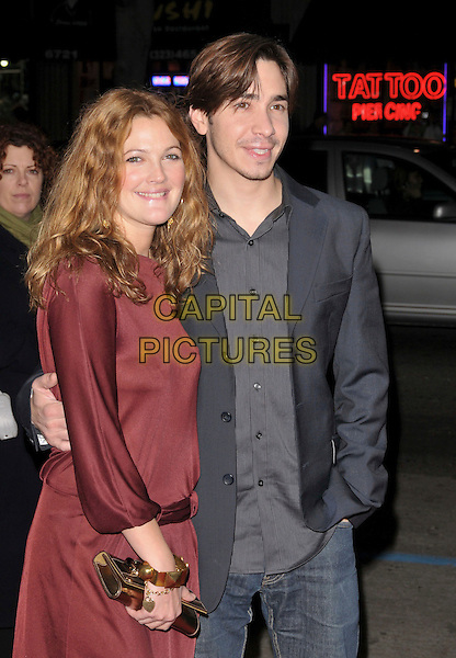 DREW BARRYMORE & JUSTN LONG.attends Picturehouse Premiere of Vince Vaughn's Wild West Comedy Show held at The Egyptian Theatre in Hollywood, California, USA,  January 28th 2008. .half length red dress maroon couple grey jacket gold clutch bag .CAP/DVS.©Debbie VanStory/Capital Pictures