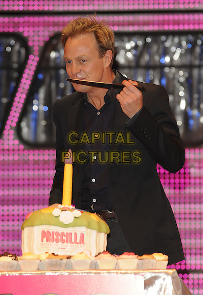 JASON DONOVAN .The cast of 'Priscilla Queen Of The Desert' celebrate their first 100 performances at the Palace Theatre, London, England..June 23rd, 2009.half length black suit jacket cutting cake knife eating funny face .CAP/CAN.©Can Nguyen/Capital Pictures.