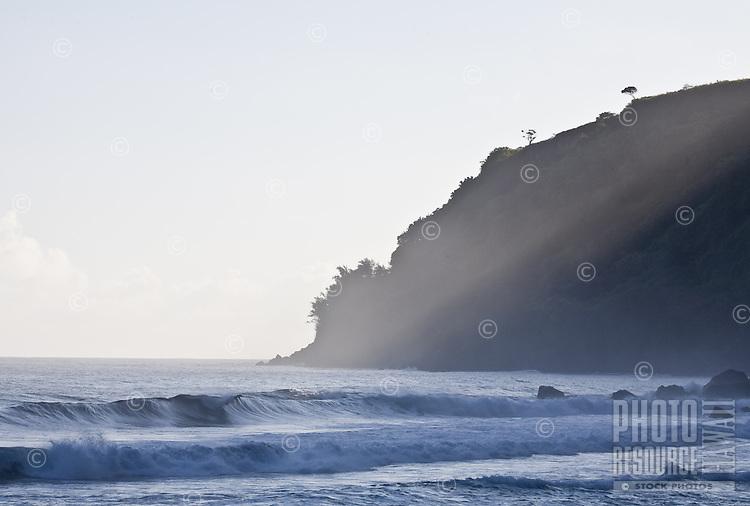 Slanting rays of afternoon sun on breaking waves in Waipio Beach