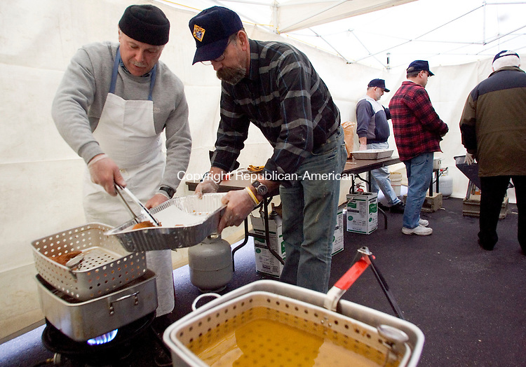 SOUTHBURY, CT- 07 MARCH 2008- 030708JT07-<br /> Southbury Knights of Columbus members Tim Kowalski and Bill Mikolsky load fried fish into a pan during Sacred Heart Church's fish fry dinner on Friday at Southbury. The Columbiettes also helped in the event.<br /> Josalee Thrift / Republican-American