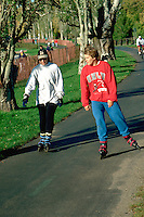 Friends age 21 rollerblading around Lake Calhoun.  Minneapolis  Minnesota USA