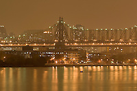 Queensboro Bridge ( also known as The 59th Street Bridge) passing over Roosevelt Island and the East River on an Overcast Night, Upper East Side of Manhattan visible in the background