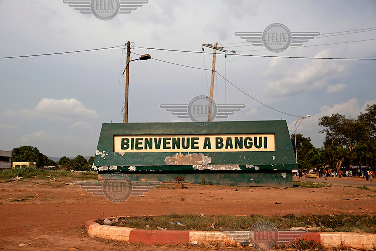 A battered 'Welcome to Bangui' sign at the roadside near the airport.