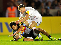 Twickenham, England.  Ollie Lindsay-Hague of Harlequins tackled by Chris Ashton of Saracens during the Aviva Premiership match between Harlequins and Saracens at Twickenham Stoop on September 12, 2014 in London, England.