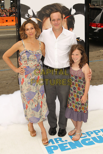 "Jennifer Grey, Clark Gregg & Stella.Los Angeles Premiere of 20th Century Fox' ""Mr. Popper's Penguins,"" at Grauman's Chinese Theatre. Hollywood, CA USA. .June 12th, 2011.full length dress side trousers white shirt arm around waist kiss kissing married husband wife gray daughter mother mom mum father dad daughter kid child family.CAP/CEL .©CelPh/Capital Pictures."