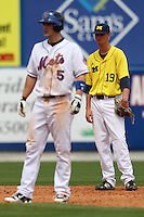 March 21, 2010:  Shortstop Derek Dennis (19) of the Michigan Wolverines in the field as David Wright (5) of the NY Mets leads off during a game at Tradition Field in St. Lucie, FL.  Photo By Mike Janes/Four Seam Images