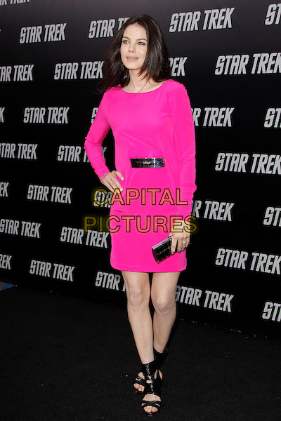 "MICHELLE MONAGHAN.The Paramount Pictures L.A. Premiere of ""Star Trek"" held at The Grauman's Chinese Theatre in Hollywood, California, USA. .April 30th, 2009.full length black dress clutch bag pink neon fluorescent ankle strap shoes sandals belt silver hand on hip.CAP/DVS.©Debbie VanStory/Capital Pictures."