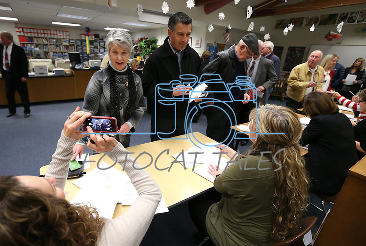Caucus volunteer Christina Sherbrook, left, takes a photo of voter Maureen Rovig as she signs in next to Gov. Brian Sandoval at the Republican caucus at Caughlin Ranch Elementary School in Reno, Nev. on Tuesday, Feb. 23, 2016. Cathleen Allison/Las Vegas Review-Journal