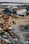 March 28, 2011, Ishonomaki, Japan - Two women are dwarfed by mounds of debris in Ishinomaki, Miyagi prefecture, on Monday, March 28, 2011, in the aftermath of killer quake and tsunami. Ishinomaki, an industrial port some 350km northeast of Tokyo, is one of the hardest-hit areas in northeast Japan by the March 11 magnitude 9.0 earthquake and the subsequent 10-meter tsunami. Much of the town still remains submerged in muddy waters, which have hampered the efforts of people searching for missing kin and reconstruction. (Photo by AFLO) [3609] -mis-