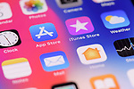 Closeup of iPhone screen with colorful app icons on desktop