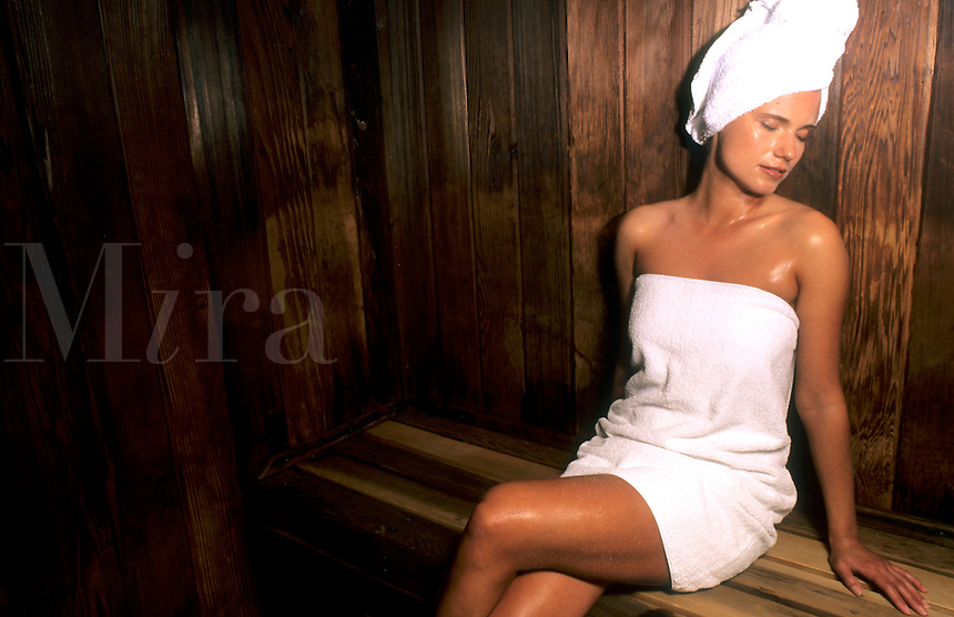 Attractive woman relaxing in resort sauna spa.