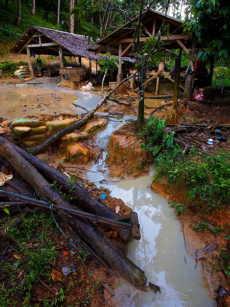 A small-scale ore processing facility in a jungle mining area.  This operation uses mercury which can leach into the runoff and find its way into nearby streams and rivers...The tumblers are loaded with coarse ore and water then tumbled for many hours until a thick sludge if formed.  The sludge is then processed to remove the gold through a process of panning and treatment with mercury...A miner tends to the rotating drums, pouring water over them periodically to keep them cooled..Story Summary:.Small-scale gold mining in the Philippines uses mercury and cyanide to extract elemental gold from ore extracted from mines and pits dug by hand.  Very young children, some as young as four, are put to work at less dangerous but still rigorous tasks in the gold mining areas.  These include panning in streams or rivers and hauling ore sacks that can weigh up to 60 pounds.  Children often play near mechanized equipment and highly toxic mercury and cyanide.  These chemicals, used to help extract elemental gold from ore, are leached into nearby watersheds where fish and other marine life, mainstays of the Philippine diet, are poisoned.  The high price of gold and the poor economy in many developing countries has led to an increase in small-scale gold mining throughout the world.