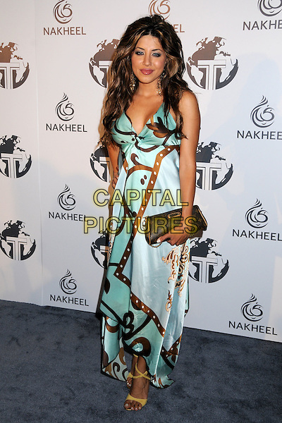 LEYLA RAZZARI .Attending The Nakheel Introduction of The Trump International Hotel & Tower Dubai held at The Tar Estate in Bel Air, California on August 23rd 2008.                                                                     .full length turquoise green brown print patterned dress clutch bag silk hand on hip.CAP/ADM/BP.©Byron Purvis/Admedia/Capital PIctures