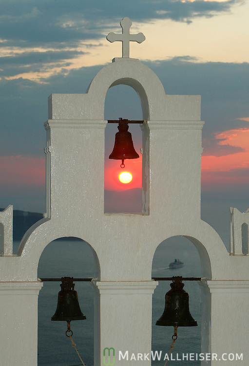 A cruise ship is seen in the steeple of one of the many churches on the island of Santorini, Greece.