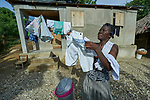 Ceneprise Etienne hangs laundry in front of her family's new home in Djondgon, a village near Jean-Rabel in northwestern Haiti. The family's previous house was destroyed during Hurricane Matthew in 2016, and Church World Service, a member of the ACT Alliance, helped the family build their sturdy new home.