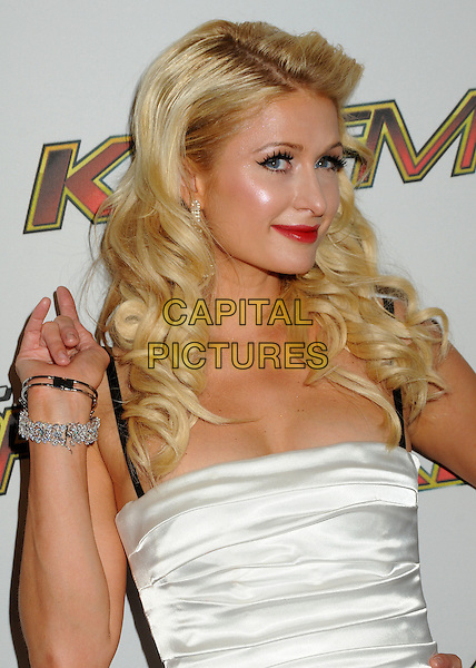 PARIS HILTON.KIIS FM's 2011 Wango Tango Concert held at the Staples Center, Los Angeles, California, USA..May 14th, 2011.half length white dress hand black red lipstick bracelets diamonds gold silk satin straps .CAP/ADM/BP.©Byron Purvis/AdMedia/Capital Pictures.