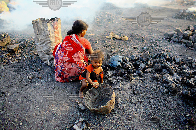 A woman prepares to make coke with coal that has been scavenged illegally from an open-cast mine near the village where a community of coal scavengers live and work. As she works her young child plays beside her. /Felix Features