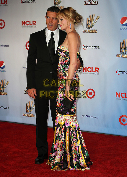 Antonio Banderas and Melanie Griffith.2011 NCLR ALMA Awards Held at The Santa Monica Civic Auditorium, Santa Monica, California, USA,.10th September 2011 .full length black suit white shirt tie print patterned red pink floral dress strapless long maxi couple husband wife .CAP/ADM/KB.©Kevan Brooks/AdMedia/Capital Pictures.