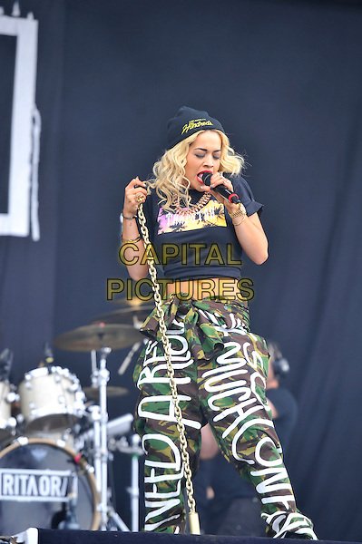 Rita Ora.performing at the Barclaycard Wireless Festival, Hyde Park, London, England. 7th July 2012..music live gig on stage show half length microphone singing black beanie hat crop top t-shirt  cropped midriff  slogan writing army green trousers camouflage 3/4 .CAP/MAR.© Martin Harris/Capital Pictures.
