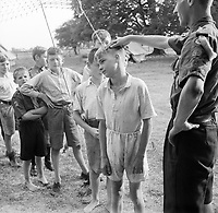 Boy Scouts queue up for their morning inspection at a fruit-picking camp near Cambridge in 1943.<br /> Boy Scouts queue up for their morning inspection at a fruit-picking camp near Cambridge. The Scout Leader checks their ears and necks to make sure they are clean before they set off for work in the plum orchards.<br /> Date 	1943