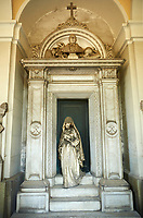 Picture and image of the stone sculpture of a women on the tomb of ship builder Giovanni Battista Piaggio by  Sculptor G. Benetti 1873. Giovanni Battista Piaggio, who is buried here, was a rich ship-owner, whose important role in society is expressed by the professional symbols -the anchor, the ropes, the sand-glass, the globe, the chart that the sculptor Giuseppe Benetti put on the sides of the deceased's bust hosted in the lunette, which surmounts the architecture in Renaissance style of the monument. As a representative of the upper middle class he couldn't die without leaving memories of his social role: Benetti, in order to meet this requirement, represented the widow coming out of the chapel with a prayer-book in her hand. Bringing the mourning in an everyday-life dimension Benetti created a work in accordance with the dictates of the Realism bourgeois. Section A, no 47, The monumental tombs of the Staglieno Monumental Cemetery, Genoa, Italy