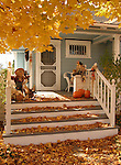 Autumn leaves cover the steps of a porch with scare crow and pumpkins, Minden, Nev.