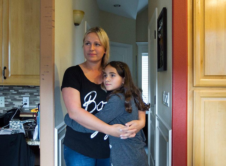 Irina Razumovsky  gets a hug from her 10-year old daughter Julie Mourao at their home in Vancouver Tuesday September 30, 2014.  Razumovsky is using the crowdfunding website Go Fund Me to raise money to buy Julie an insulin pump for her 11th birthday next month.  (Natalie Behring/for the Columbian)