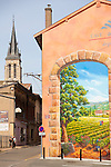 The Wine Route in early spring in Beaujolais, France. The village of Fleurie, one of the ten crus of Beaujolais.  The town square is dominated by a church, and a few restaurants which serve regional cuisine.