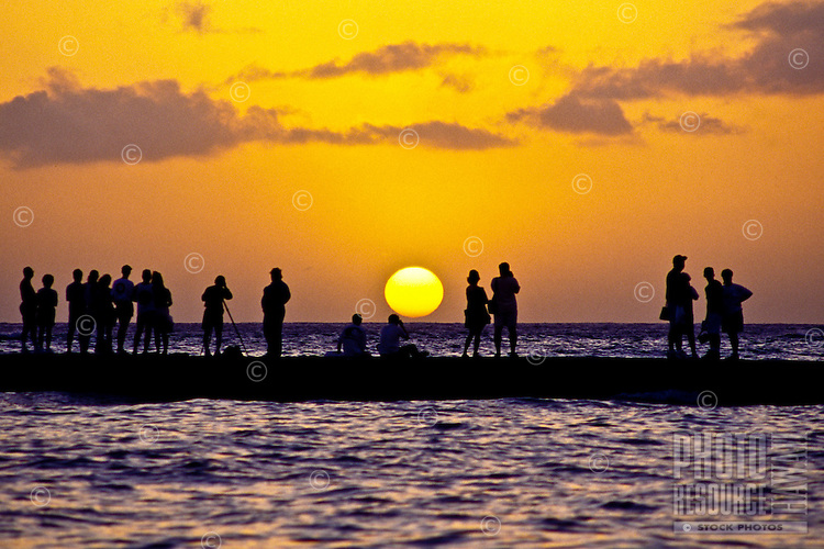 Tourists gather to witness another spectacular sunset off Waikiki Beach, Oahu