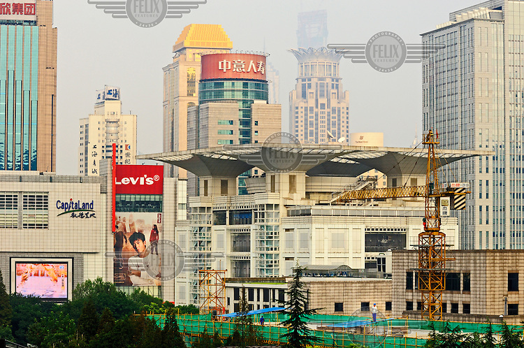 City centre view, with construction, advertising for Levi's and the distinctive Shanghai Urban Planning Exhibition Hall at centre.